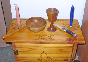 Wiccan altar with candles, chalice, cauldron (bowl), wand, and athame