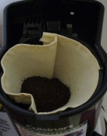 Folgers ground coffee in a washable muslin coffee filter.