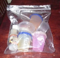 1 oz tupperware cups for allowed foodstuffs and 2 oz disposable salad dressing cups for USA only sauces and salad dressings readily fit in your 1 quart zipper bag.